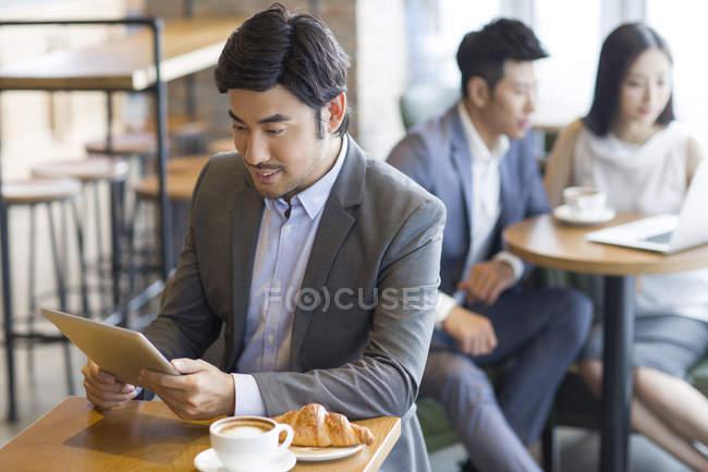 Homme d'affaires chinois utilisant une tablette numérique dans un café — Photo de stock