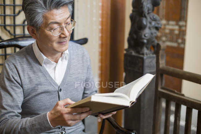 Senior Chinese man sitting in chair and reading book — Stock Photo