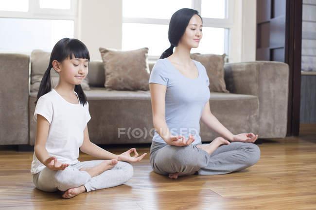 Китайская мать и дочь медитируют дома — стоковое фото