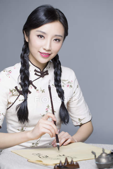 Chinese woman in traditional dress practicing calligraphy — Stock Photo