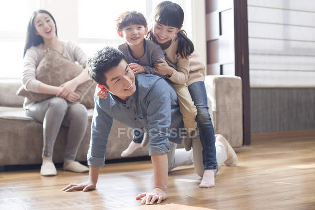 Chinese kids playing with father on floor while mother laughing on sofa — Stock Photo