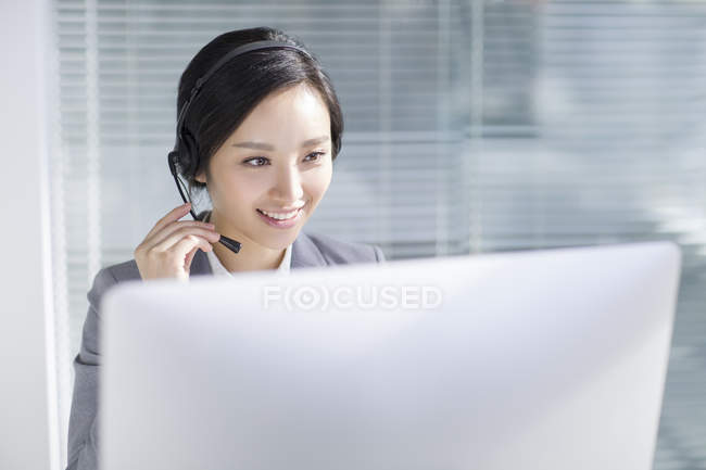 Chinese businesswoman using headset at workplace — Stock Photo
