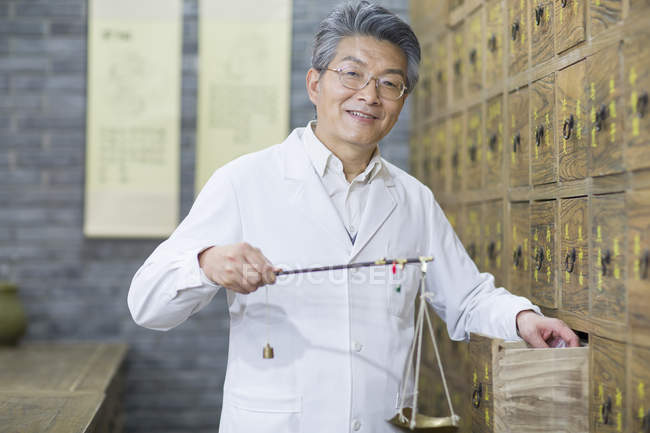 Chinese pharmacist standing with weight scale at open drawer — Stock Photo