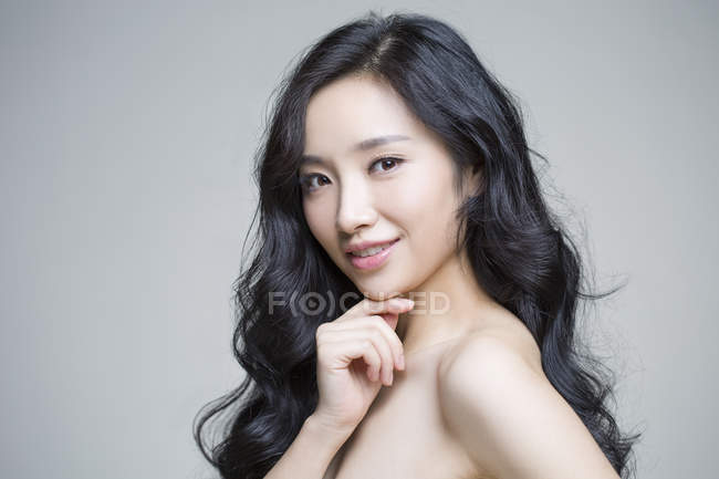 Chinese woman posing with hand on chin — Stock Photo