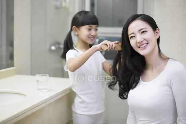 Chinesisches Mädchen kämmt Mutter Haare im Badezimmer — Stockfoto