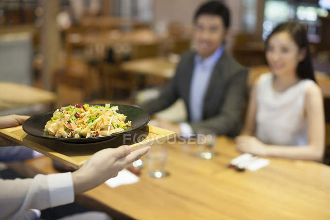 Waitress serving food in restaurant — Stock Photo