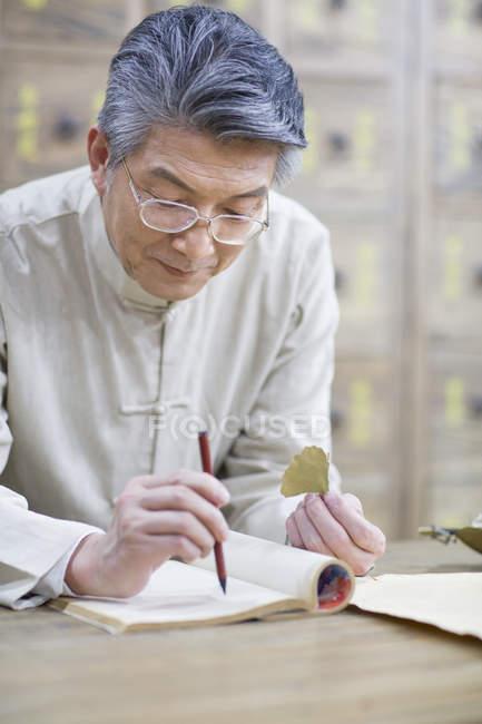 Старший Китайська лікаря-Холдинг лікарські трави і писати в Блокноті — стокове фото