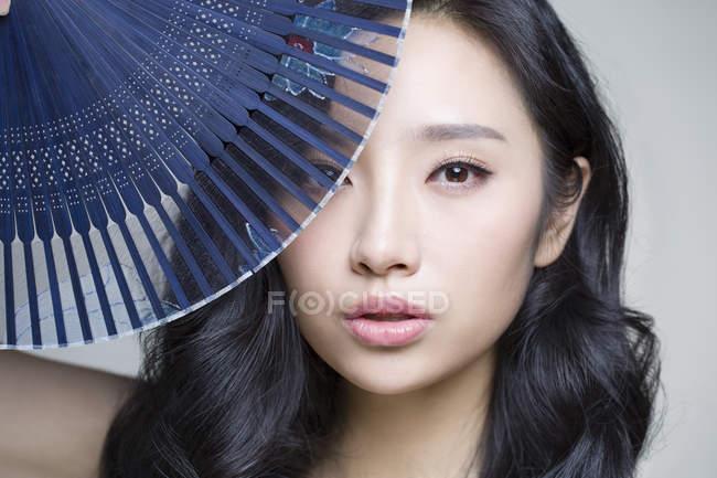 Китаянка, прикрывающая лицо складным вентилятором — стоковое фото