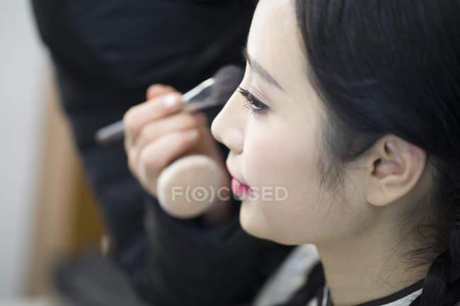 Makeup artist applying powder to young woman face — Stock Photo