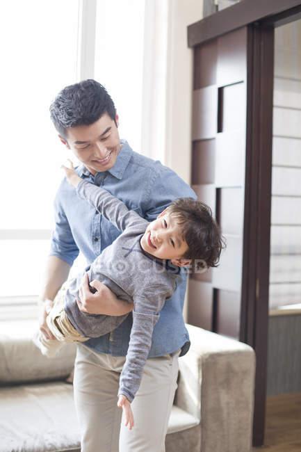 Père chinois jouant et tenant son fils à la maison — Photo de stock