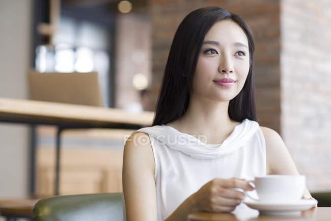 Китайська жінка, що сидить з кава і дивитися вбік — стокове фото