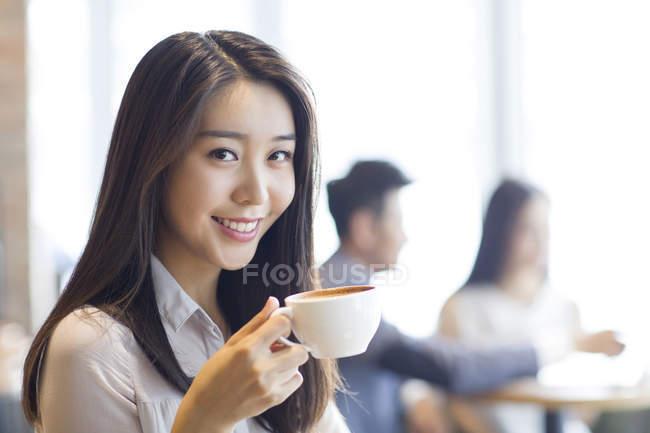 Китайська жінка, що п'ють кави в кафе — стокове фото