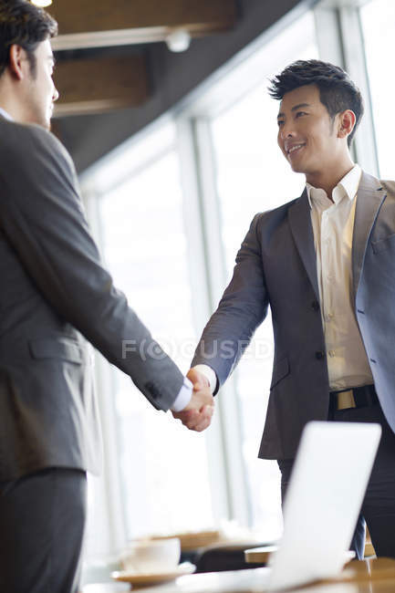 Chinese businessmen shaking hands in coffee shop — Stock Photo