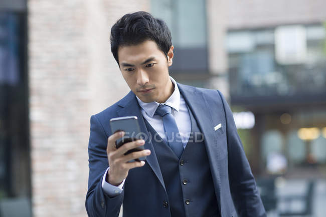 Chinese businessman using smartphone on street — Stock Photo
