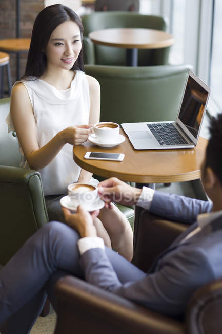 Chinese business people talking with coffee and laptop — Stock Photo