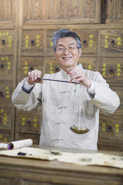 Farmacista cinese che sta con la scala del peso in farmacia — Foto stock