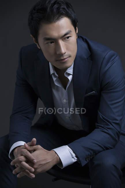 Портрет впевнено китайський бізнесмен сидить з руки — стокове фото