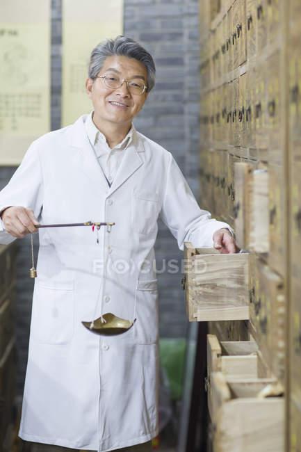 Farmacista cinese che sta con la scala del peso al cassetto aperto — Foto stock