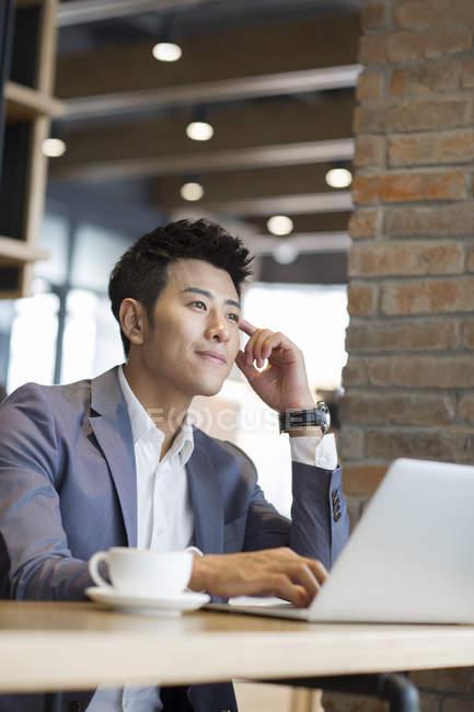 Uomo d'affari cinese che si siede con il computer portatile in caffè — Foto stock