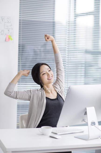 Китайська жінка розтягування і розслабляючий в офісі — стокове фото