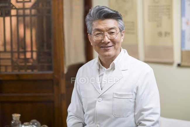 Leitender chinesischer Arzt steht in Klinik und schaut in die Kamera — Stockfoto