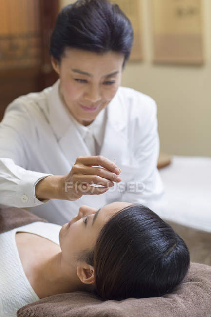 Mature woman performing acupuncture treatment on female face — Stock Photo