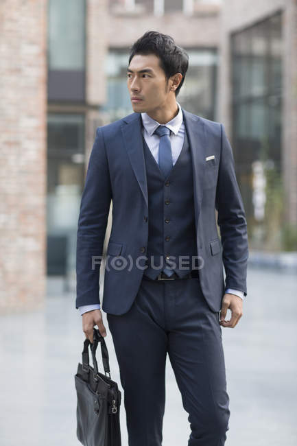 Chinese businessman standing on street with briefcase — Stock Photo
