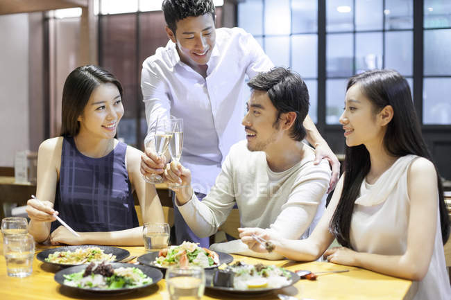 Chinese friends clinking glasses in restaurant — Stock Photo