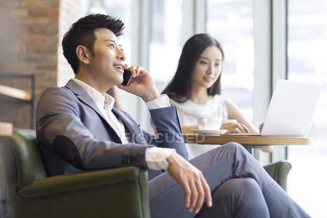 Uomo cinese che comunica sul telefono con donna con portatile — Foto stock