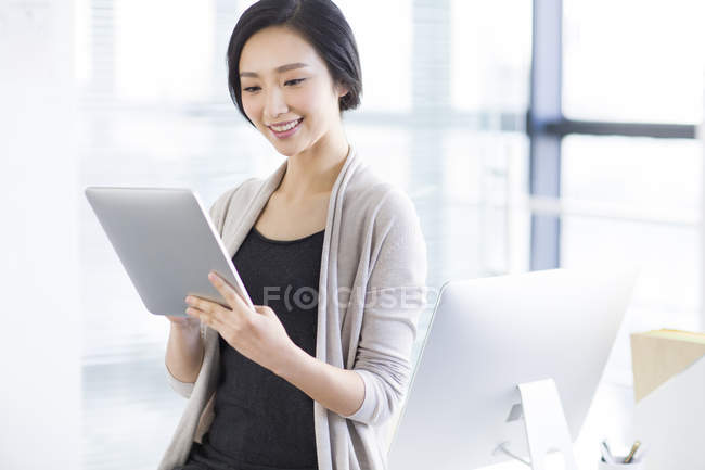 Chinese woman using digital tablet in office — Stock Photo