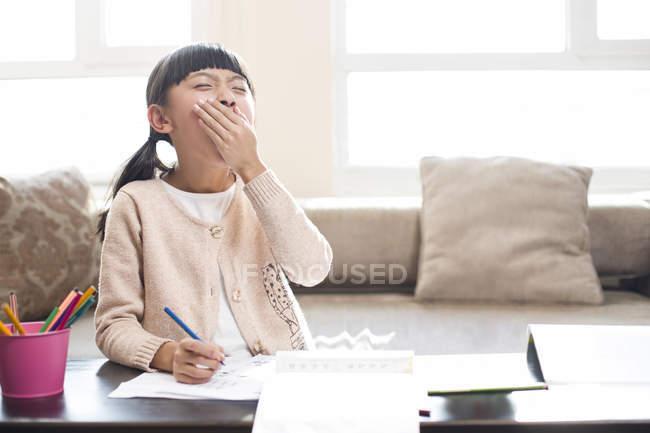 Menina chinesa cansada bocejando enquanto fazendo lição de casa — Fotografia de Stock