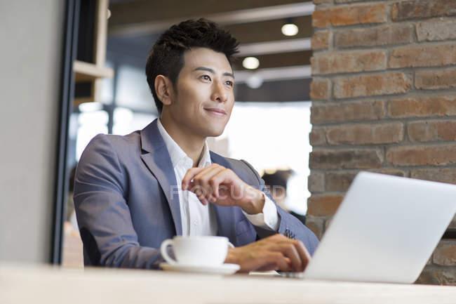 Homme d'affaires chinois assis avec ordinateur portable dans un café — Photo de stock