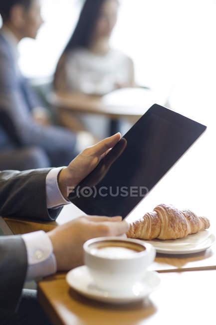 Закри чоловічої руки, використовуючи цифровий планшетний в кафе — стокове фото