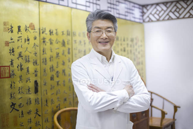 Senior chinese doctor standing with arms folded — Stock Photo
