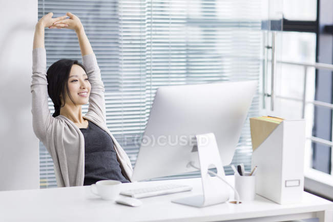 Chinese woman stretching arms in office and looking through window — Stock Photo