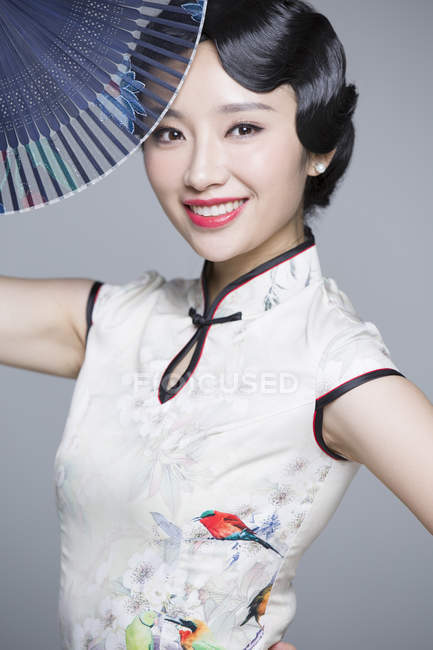 Chinese woman in traditional cheongsam posing with folding fan — Stock Photo