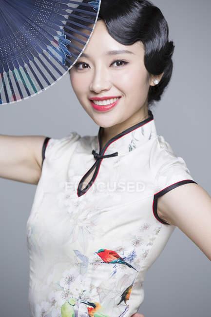 Китаянка в традиционном чхонсам позирует с раскладывающимся вентилятором — стоковое фото