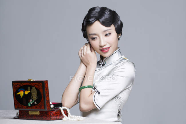 Chinese woman in traditional dress putting on earrings — Stock Photo