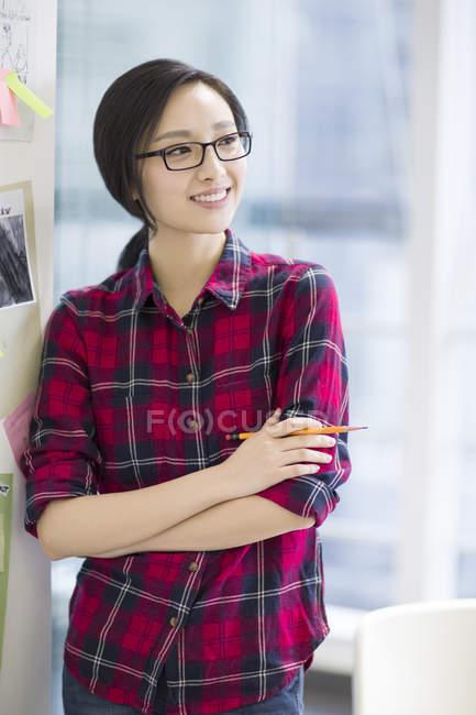 Designer chinesa em pé na parede com esboços — Fotografia de Stock