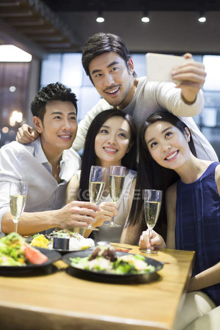 Friends taking selfie with smartphone in restaurant — Stock Photo