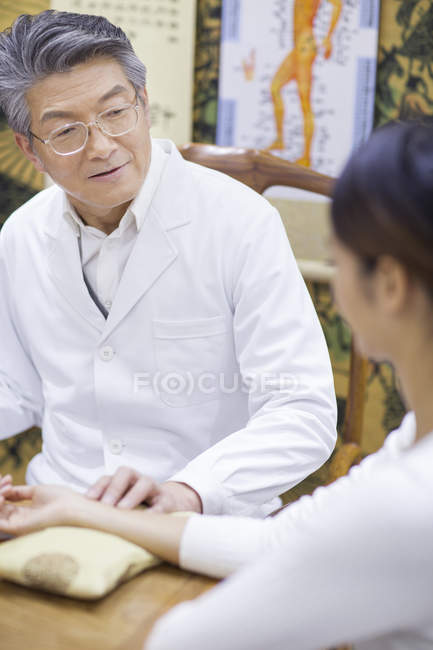 Senior Chinese doctor taking the pulse of patient — Stock Photo