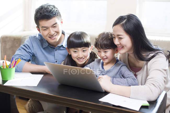 Chinese parents with kids using laptop in living room — Stock Photo
