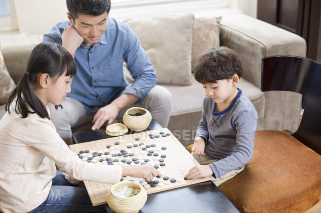 Chinese children playing the game of Go while father watching on sofa — Stock Photo