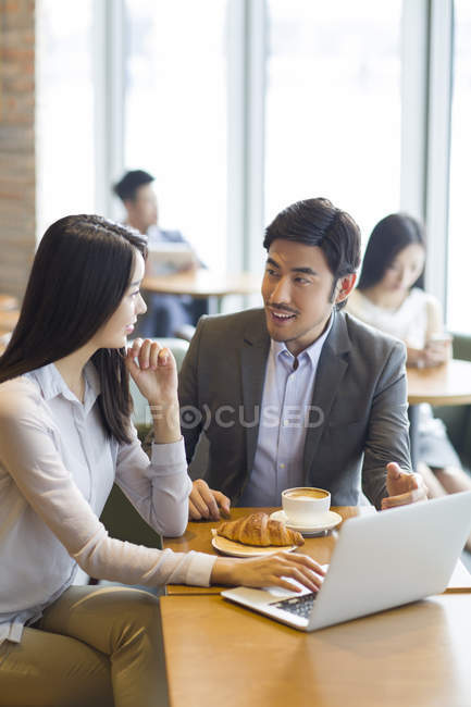 Chinese business people sitting and talking with laptop in cafe — Stock Photo
