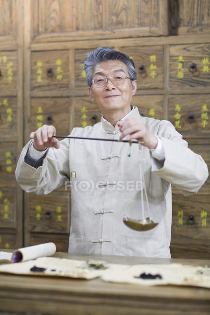 Chinese pharmacist standing with weight scale in pharmacy — Stock Photo