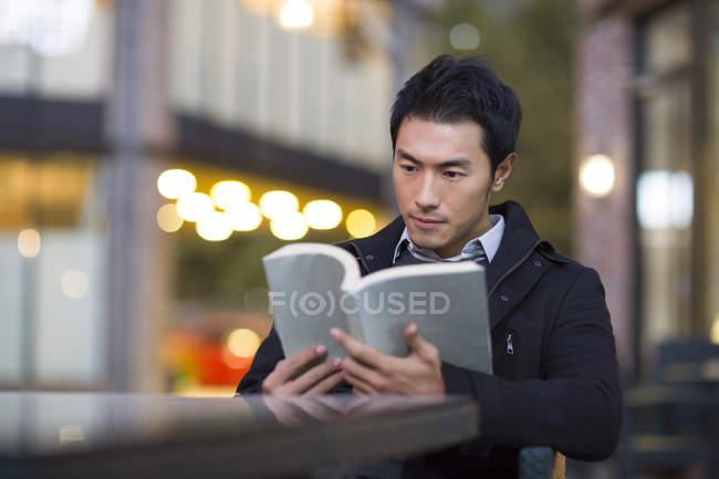 Chinesischer Mann Lesebuch im Straßencafé — Stockfoto