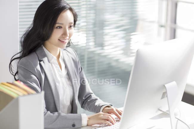 Китайський бізнес-леді за допомогою комп'ютера в офісі — стокове фото