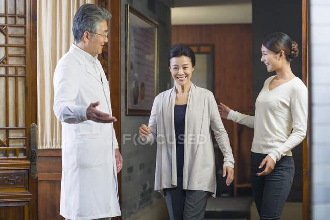 Médico chino mayor dando la bienvenida a los pacientes en el pasillo - foto de stock