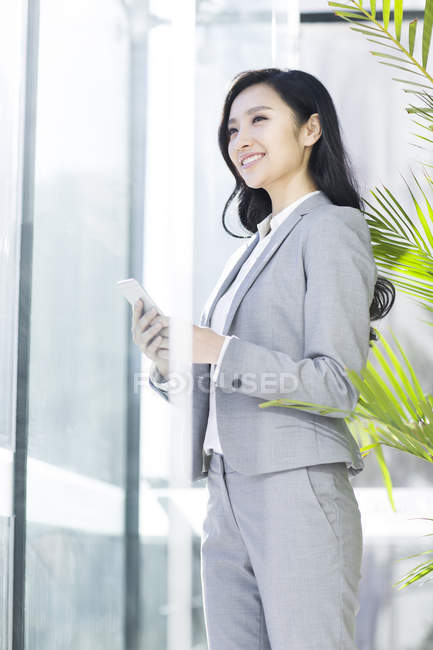 Chinese businesswoman holding smartphone and looking away at office — Stock Photo