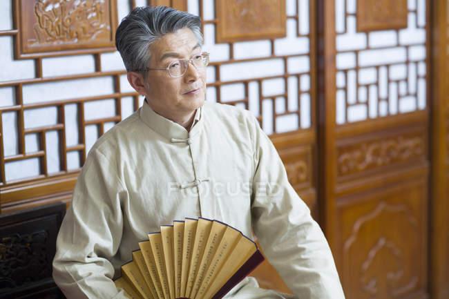 Sênior chinês homem segurando vintage ventilador portátil no interior tradicional — Fotografia de Stock